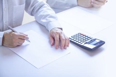 Businessmen in a meeting room partially cropped at their hands holding a pen with writing gesture on a plain blank white paper document as a blank mock-up template to be refilled with any information.