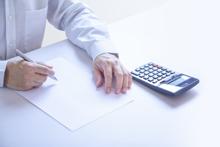 Business man partially cropped at his hands holding a pen in writing gesture on a plain blank white paper document with a calculator as a blank mock-up template to be refilled with any information. 写真素材