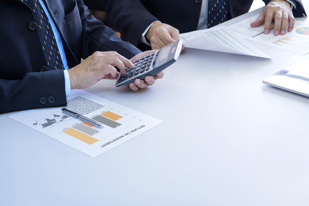 Two businessmen are deeply reviewing a financial reports for a return on investment or investment risk analysis on a white desk. Lower right copy space included.