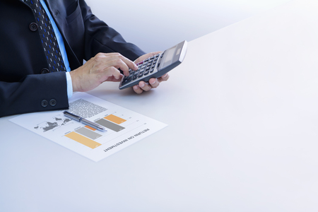 Businessmen isolated on white using calculator reviewing financial report for a return on investment or investment risk analysis on a white desk. Right copy space included.