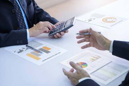 Two businessmen are deeply reviewing a financial reports for a return on investment or investment risk analysis on a white desk. Upper and lower right copy spaces included. Reklamní fotografie