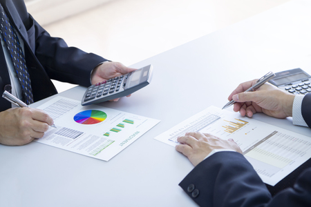 Two businessmen are deeply reviewing a financial reports for a return on investment or investment risk analysis on a white desk. Upper copy space included.