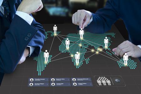 Deux administrateurs d'entreprise déplaçant un pion sur une carte numérique en tant que tableau de bord virtuel formant un concept de planification de stratégie de travail d'équipe et d'expansion commerciale.