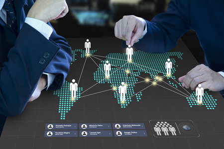 Two business administrator moving a pawn on a digital map as a virtual dashboard formng a business teamwork and business expansion strategy planning concept.