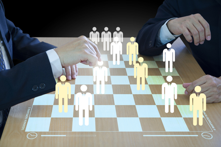 Three business administrators playing checkers or draughts on a wooden virtual checkerboad or draughtboard in concept of manpower or human resource strategy planning to form a teamwork.