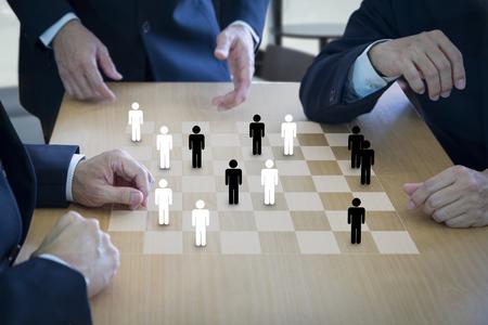 Drei Geschäftsadministratoren, die Checker oder Entwürfe auf einem hölzernen Schachbrett oder einem Entwurfsbrett spielen, im Konzept der Personal- oder Personalstrategieplanung, um eine Teamarbeit zu bilden. Standard-Bild