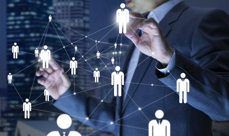 Administrador de empresas en acción de planificación de recursos humanos o mano de obra u organización empresarial en un tablero virtual. Foto de archivo