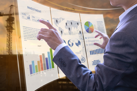 Businessman in front of modern virtual touch screen analysing on investment risk management and return on investment analysis on real estate building contruction.