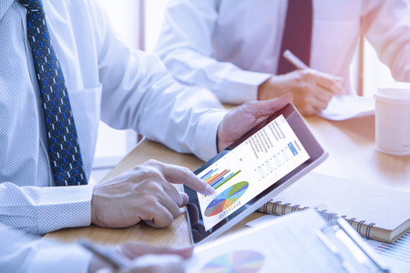 Businessmen tab on tablet touch screen to deeply reviewing a diagram or chart and financial reports for a return on investment or investment risk analysis or business performance. Reklamní fotografie