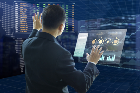 Businessman touches virtual screens analysing on investment risk managment and return on investment, ROI, analysis with fictitious stock symbols. Reklamní fotografie