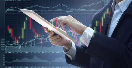 Businessman touching a tablet touch screen reviewing business investment risk analysis, return on investment - ROI, with stock and security charts.