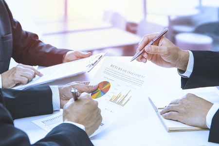 Businessmen are reviewing a financial reports for a return on investment or investment risk analysis. Reklamní fotografie