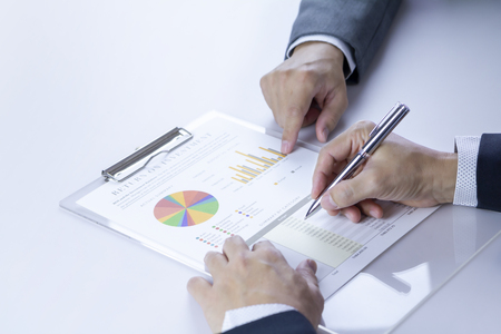 Two businessmen or analysts reviewing financial statement report on Return on Investment, ROI, or investment risk analysis and business performance.