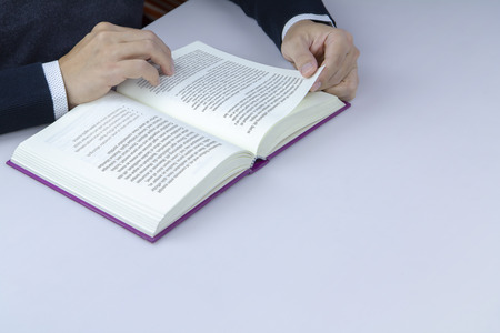 Close-up of a man reading a book in library. Isolated on white desktop and composed on a top-left corner with copy space on lower right with fictitious content on both pages.