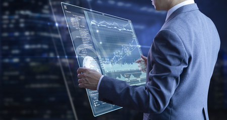 Businessman holding a modern tablet touch screen analysing on investment risk managment and return on investment analysis Reklamní fotografie