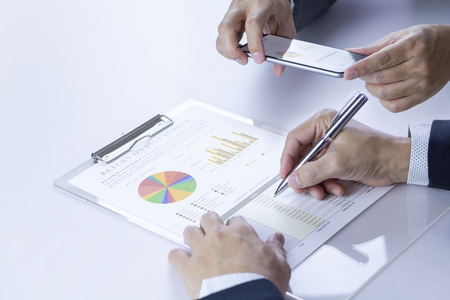 Two businessmen or analysts taking a photograph while reviewing financial statement report on Return on Investment, ROI, or investment risk analysis and business performance.