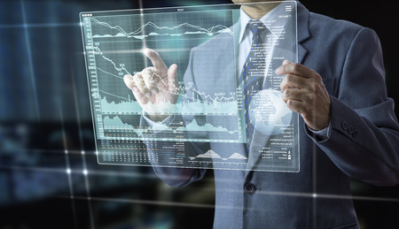 Businessman holding a futuristic modern tablet touch screen analysing on investment risk managment and return on investment analysis Reklamní fotografie