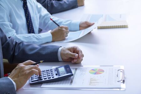 Businessmen in a meeting room are deeply reviewing financial statements and reports for a return on investment or investment risk analysis.