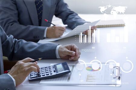 Two businessmen in a meeting room are deeply reviewing financial statements and reports for a return on investment or investment risk analysis.