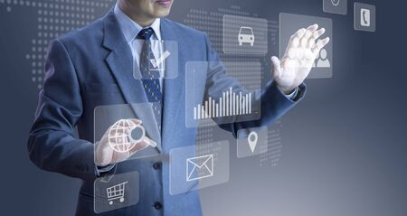Businessman touching futuristic modern virtual touch screens of a cloud system, selecting items in an application Reklamní fotografie