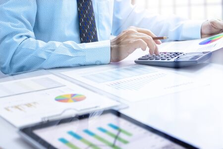 Businessman touching calcolator buttons while deeply reviewing a financial reports for a return on investment or investment risk analysis and performance.