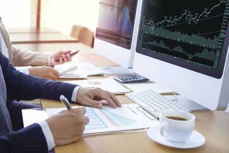Two analysts or businessmen in front of modern computer screens reviewing graphs and financial reports for stock trading or return on investment.