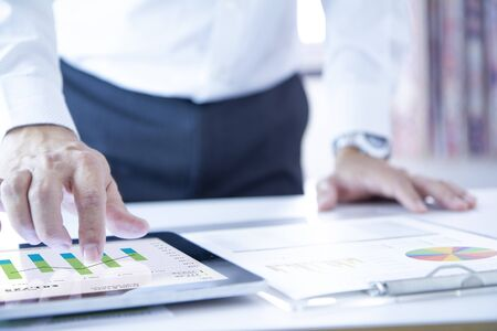 Business man touching a tablet touch screen analysing on business performance reports and returning on investment, ROI, or investment risk analysis. Reklamní fotografie