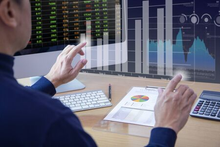 Male analyst touching twin-bar chart on virtual screen while reviewing financial statement for a retual on investment, ROI, or investment risk analysis. Reklamní fotografie