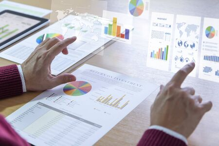 Businessman interacts with augmented reality graphics while deeply reviewing a financial report for a return on investment or investment risk analysis. Stock Photo
