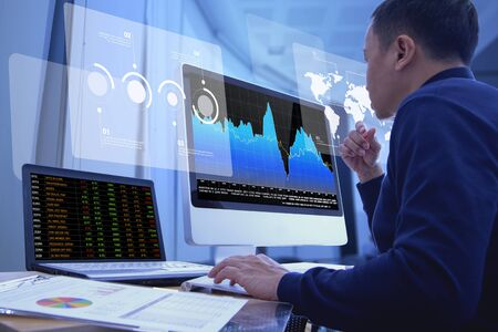 Business man looking into a modern computer screen deeply reviewing a financial report for a return on investment or investment risk analysis.