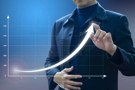 Geschäftsmann zeichnet eine exponentielle Kurve eines Fortschritts in der Unternehmenswachstumsleistung, Kapitalrendite - ROI, auf einer virtuellen Bildschirmpräsentation.