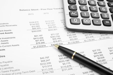 business financial chart analysis with calculator & pen on paper work