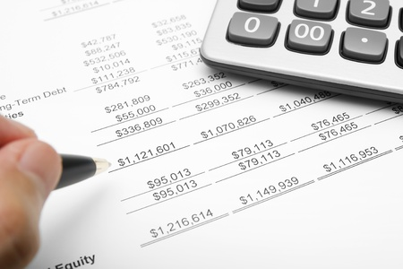 financial paperwork: business financial chart analysis with calculator, pen & hand on paper work Stock Photo