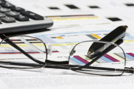 business financial chart analysis with pen eyeglasses & calculator on paper work