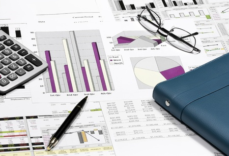 business financial chart analysis with pen, eyeglasses, calculator & notebook on paper work