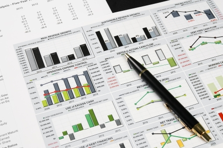 business financial chart analysis with pen on paper work