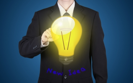 believable: finger of businessman press to bulb with new idea reflect paint on suit, blue background Stock Photo