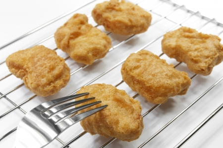 chicken nuggets with fork on grille, white background