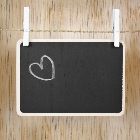 Hand drawing heart on blackboard in wood case photo