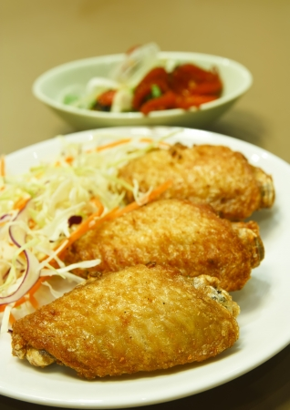 fried chicken with vegetable & spicy squid salad at japanese restaurant photo