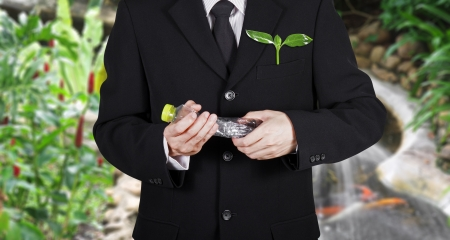 plentifully: businessman with green seedling in the pocket destroy plastic bottle  for environment on plentifully garden background