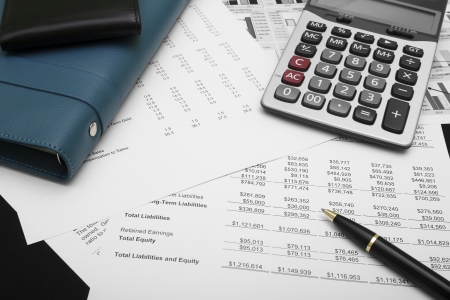 business financial chart analysis with pen, notebook, calculator & wallet on paper work