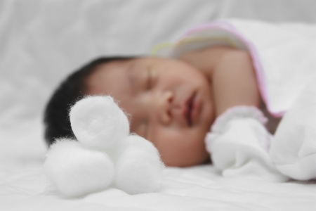 clean cotton for sanitation with newborn baby sleeping on white bed photo