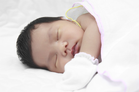 infant sleeping on white bed photo