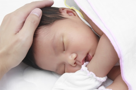 infant sleeping on white bed after drink milk photo