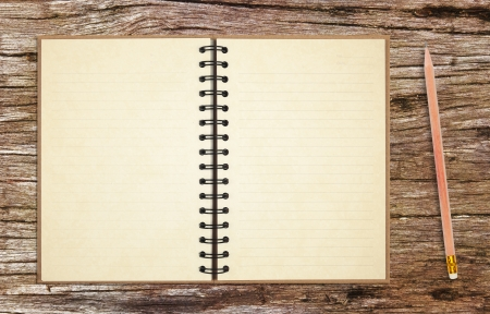 old notebook with pencil on ancient wooden table background Stockfoto