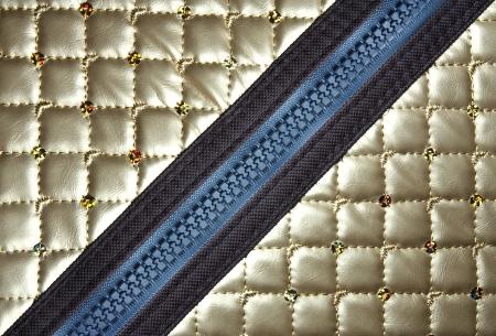 gouden lederen textuur met diagonale rits voor achtergrond Stockfoto