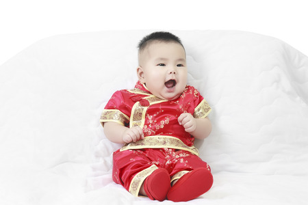 cheerful baby wearing cheongsam suit for Chinese New Year in studio