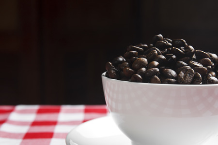 close up beans coffee in white cup on the table