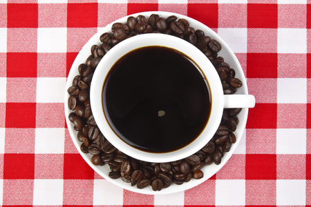 dark coffee with beans in white cup on the table Stock Photo